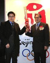 霍震霆携长子霍启刚在北京奥运会火炬展品前留影
